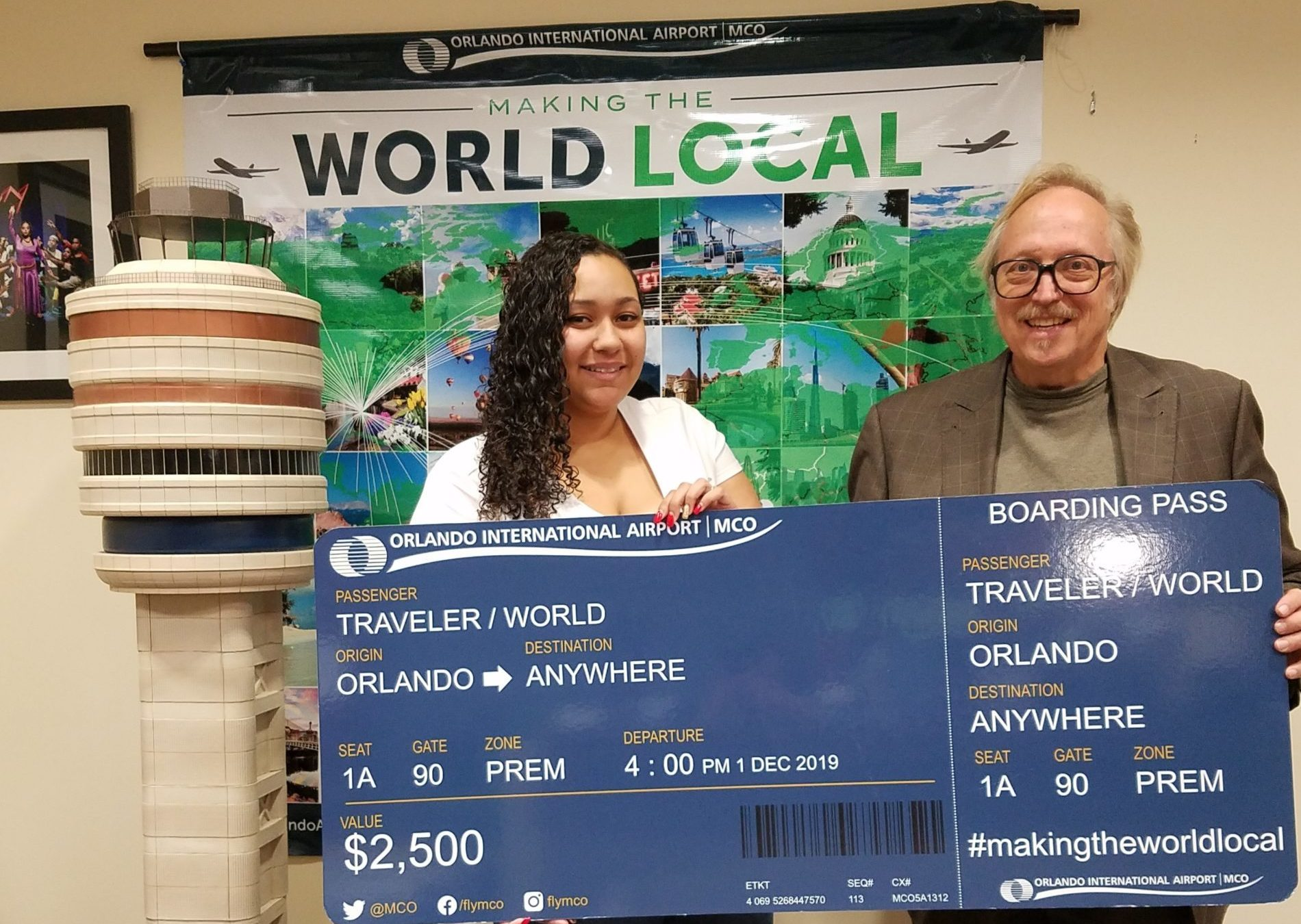Two people holding an enlarged flight ticket