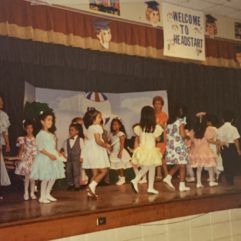 """Schoolchildren performing onstage. The words """"Welcome to Head Start"""" are above them."""