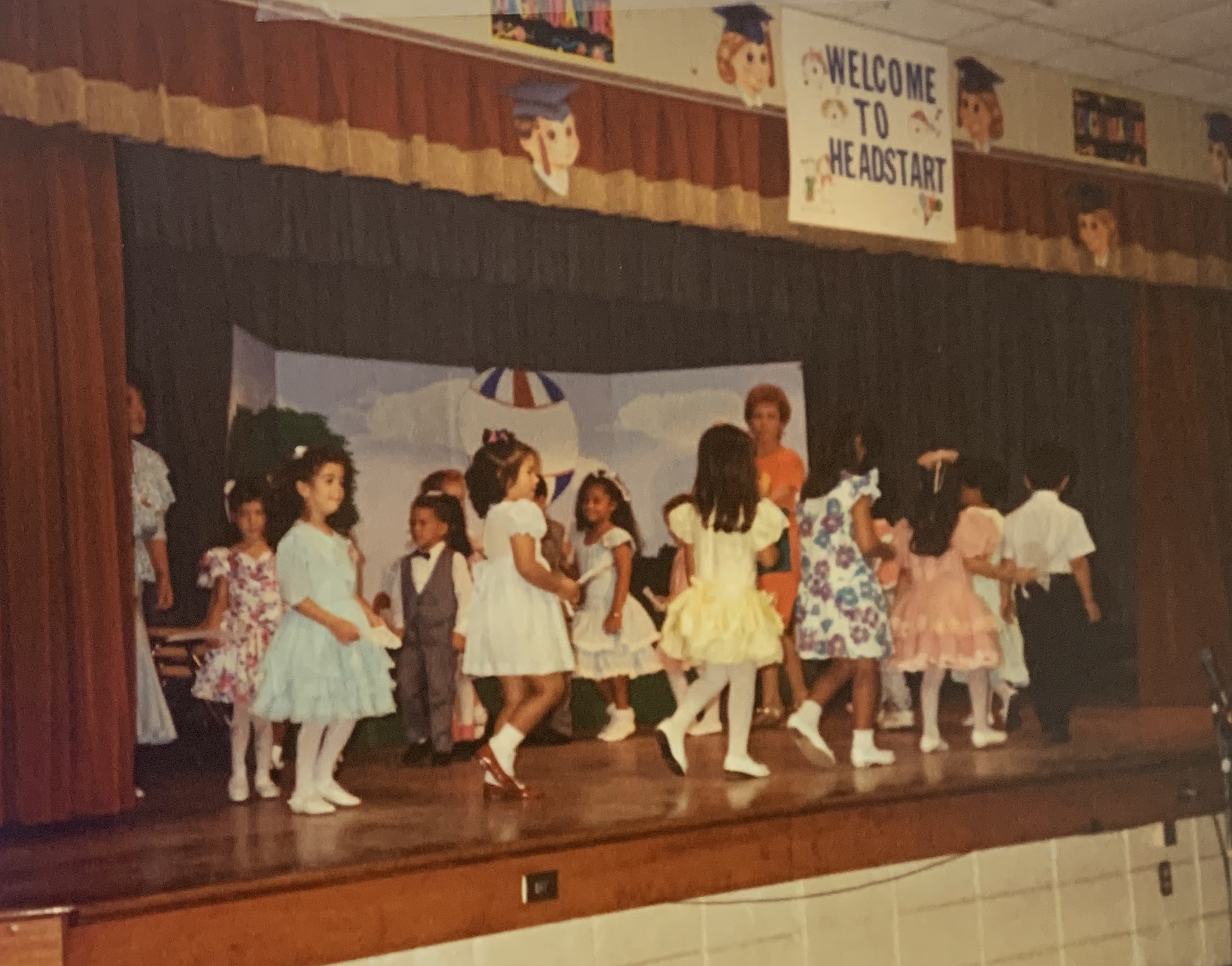"Schoolchildren performing onstage. The words ""Welcome to Head Start"" are above them."
