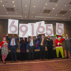 Business leaders holding signs with numbers on them representing a total number of fundraising dollars