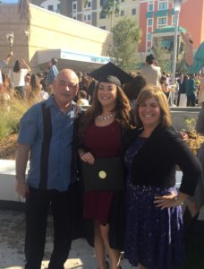 Yesenia and her parents standing for a graduation photo
