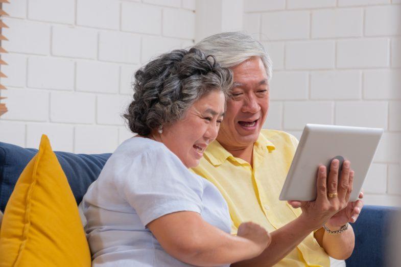 Una pareja asiática de la tercera edad usa una tablet para hacer una videollamada y hablar con su nieto.
