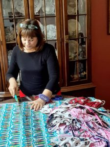 Jennifer Brinkley standing at a worktable cutting fabric with a pile of face masks next to her