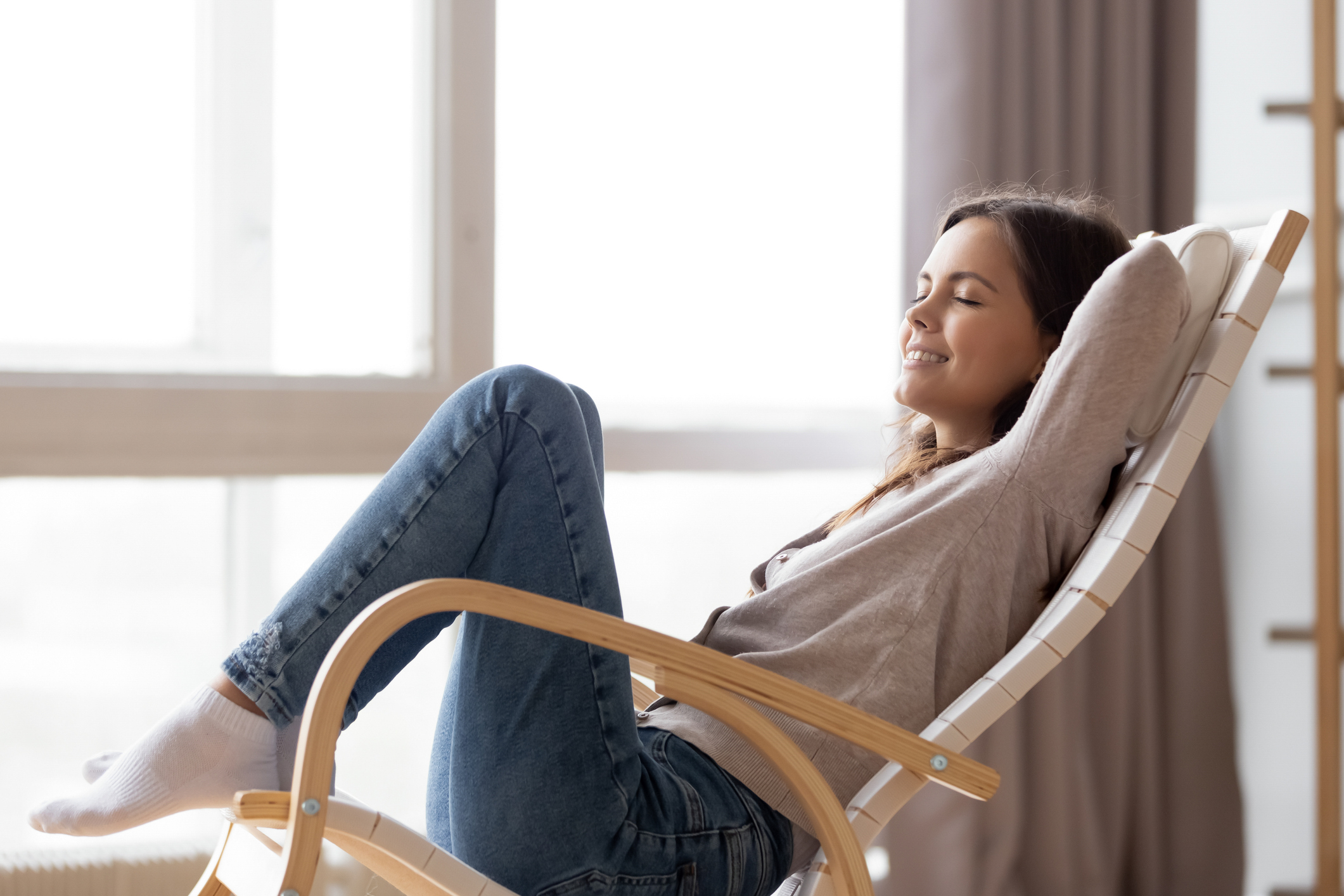 Relaxed calm young woman lounging sitting in comfortable rocking chair