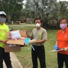 Tres personas con mascarillas; una persona sostiene una caja de suministros junto a la otra.