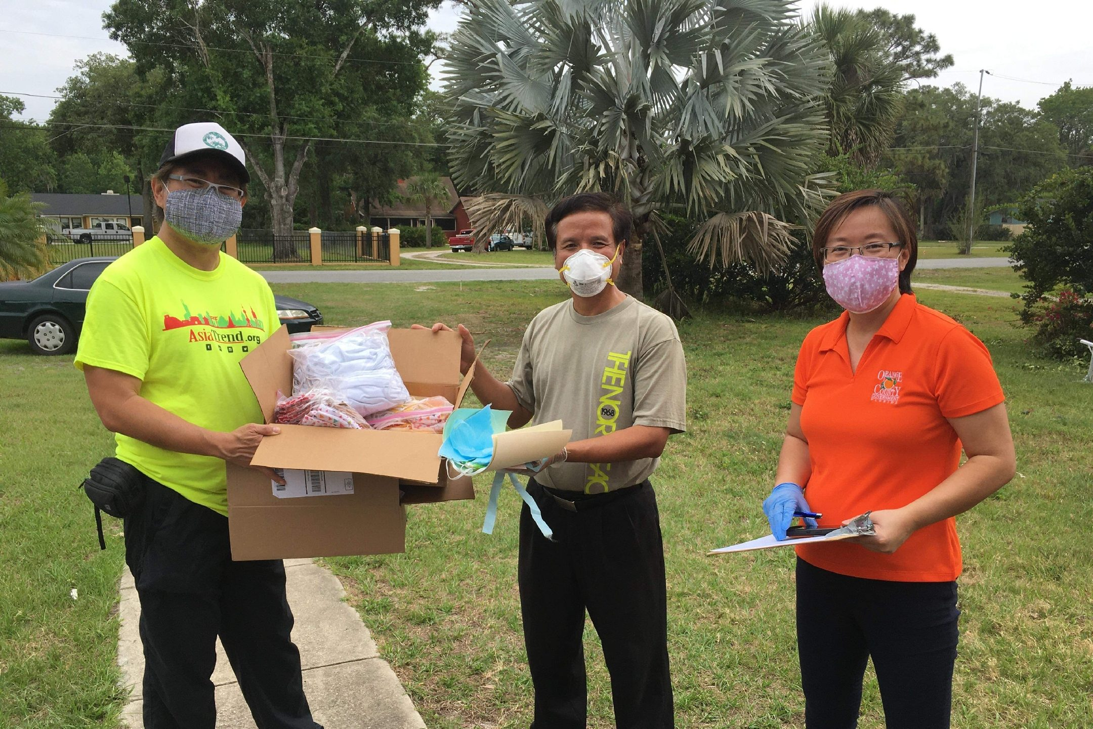 Three people wearing masks; one is handing a box of supplies to the other.