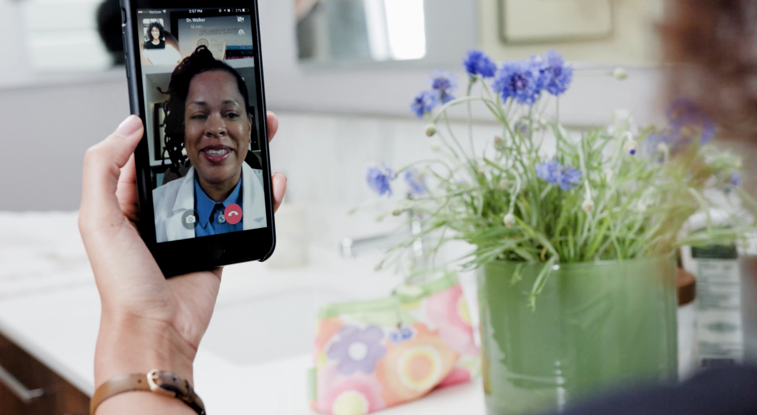 Person speaking with their doctor face to face via a cell phone