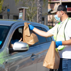 Orange County Family Services Program Manager Ben Pacquin hands a free PPE kit to a local small business at a designed drive-through pick-up location.
