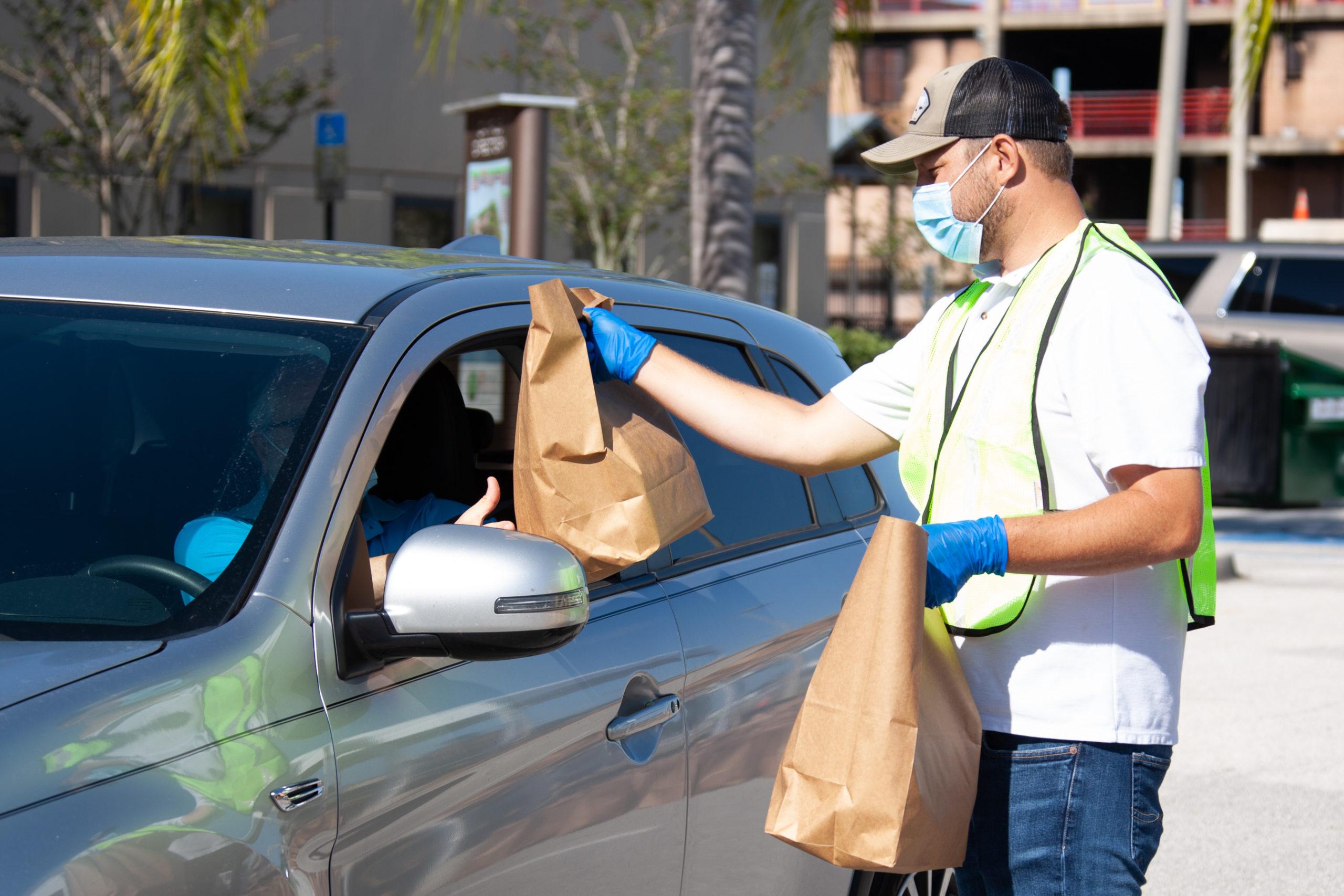 El Gerente del Programa de Servicios para la Familia del Condado de Orange,Ben Pacquin, entrega un kit de EPP gratis para un pequeño comercio local en un punto de entrega designadopara recoger desde el auto.
