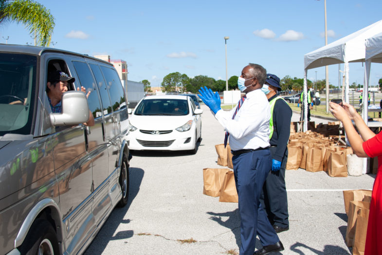 Mayor Demings handing supplies to a person driving through a distribution site