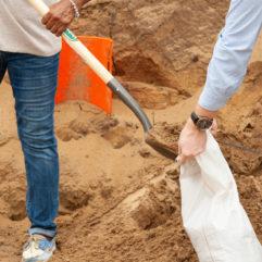 Dos personas llenando a paladas una bolsa con arena.