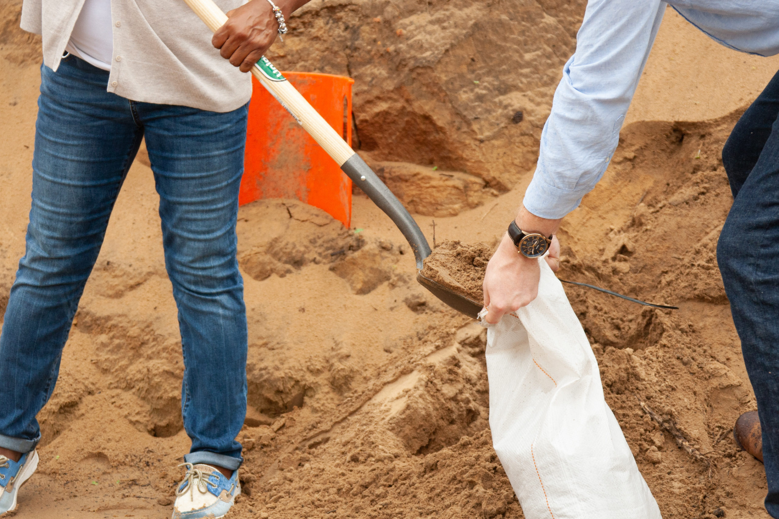 Two people shoveling sand into a bag to create a sandbag