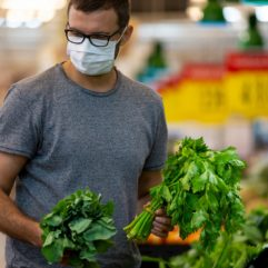 Man grocery shopping while wearing a mask