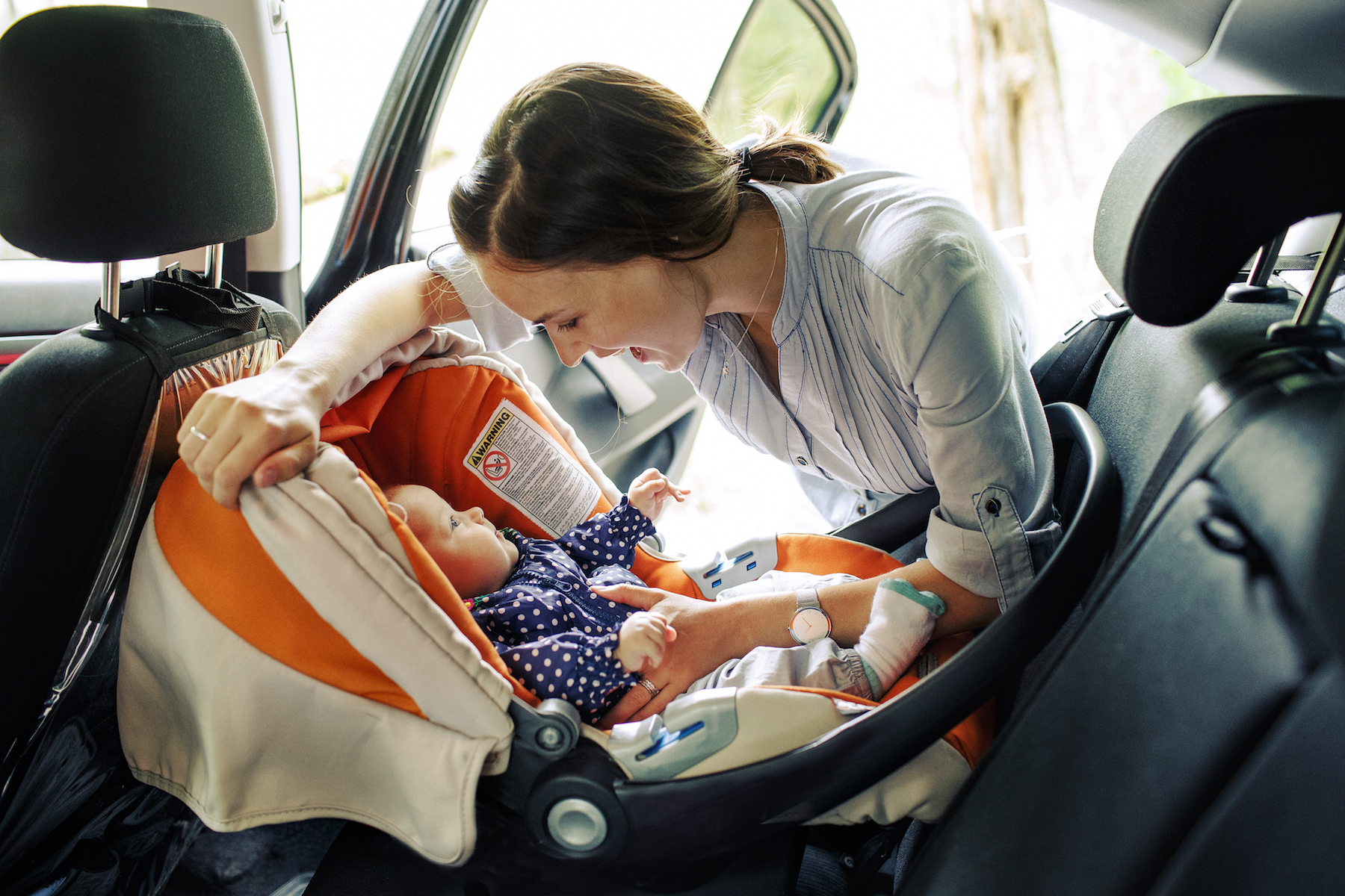 mother in a car adjusting a child seat with a baby in it.