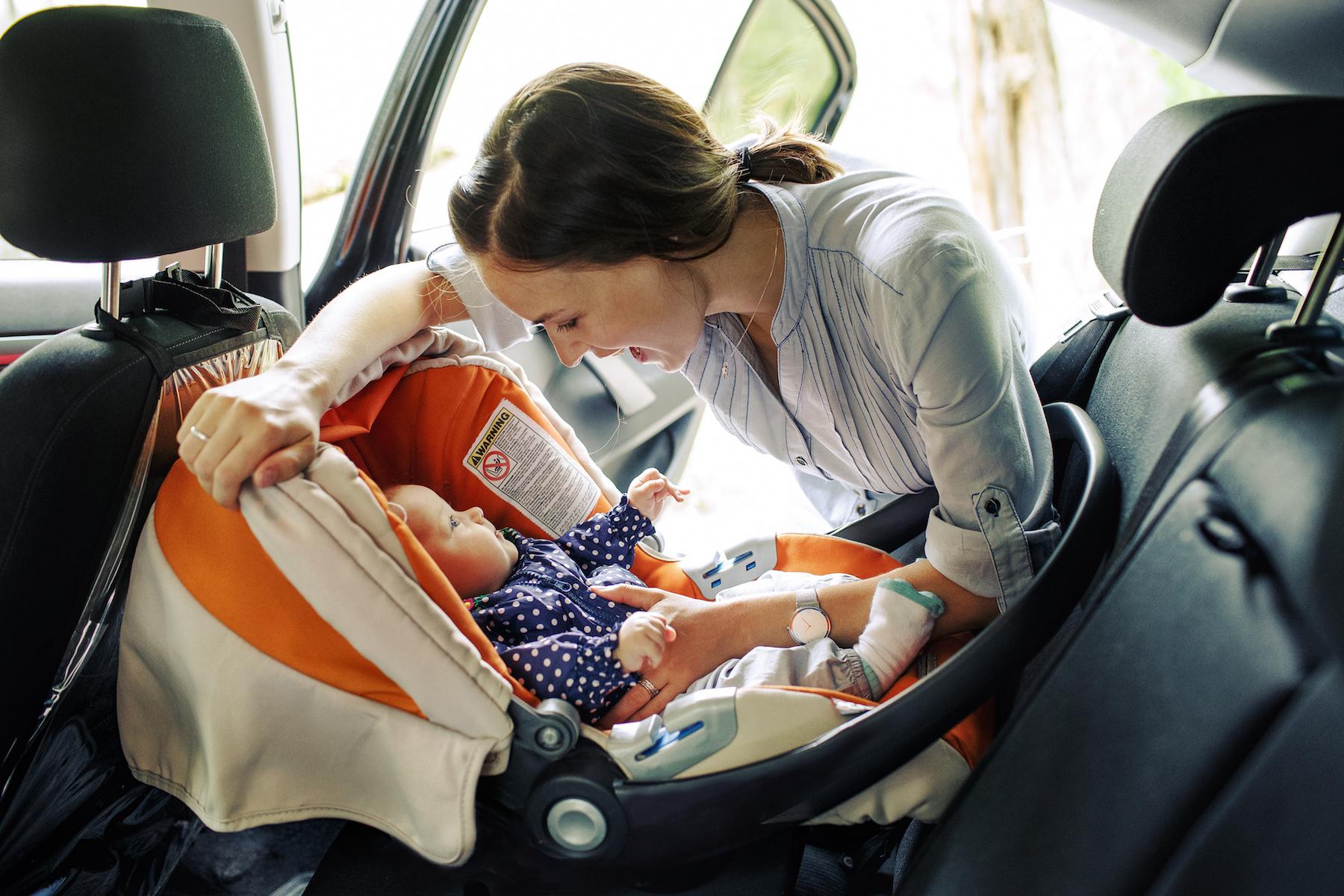 una madre en un auto ajustando el cinturón de seguridad del asiento del bebé.