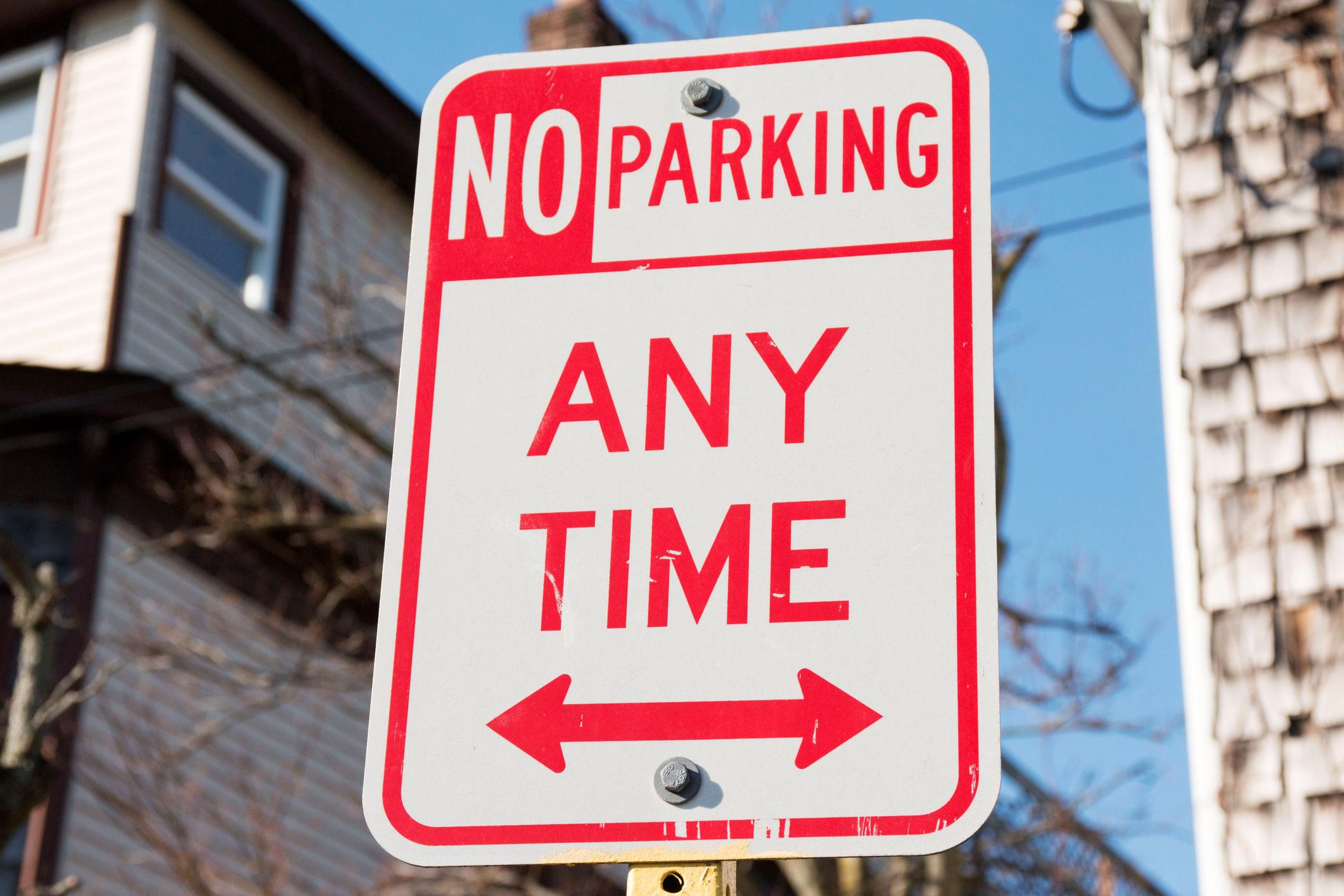 """Cartel que dice """"No parking any time"""" (Prohibido estacionar las 24 hs) en un pueblo local"""