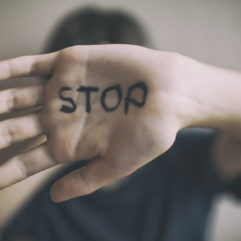 A man protects himself with his hand with. The word Stop is written on his hand.