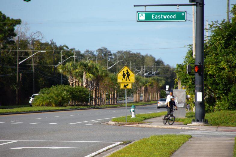 Boy riding bicycle next to a crosswalk