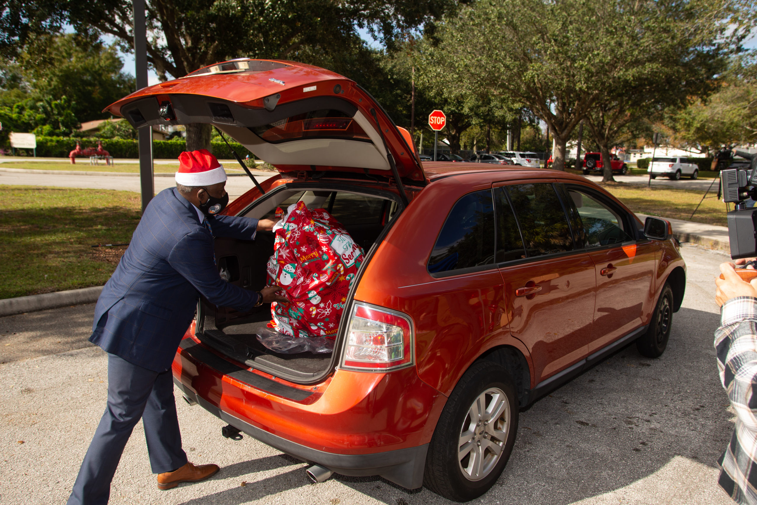 Mayor Demings loads toys into car for toy drive.