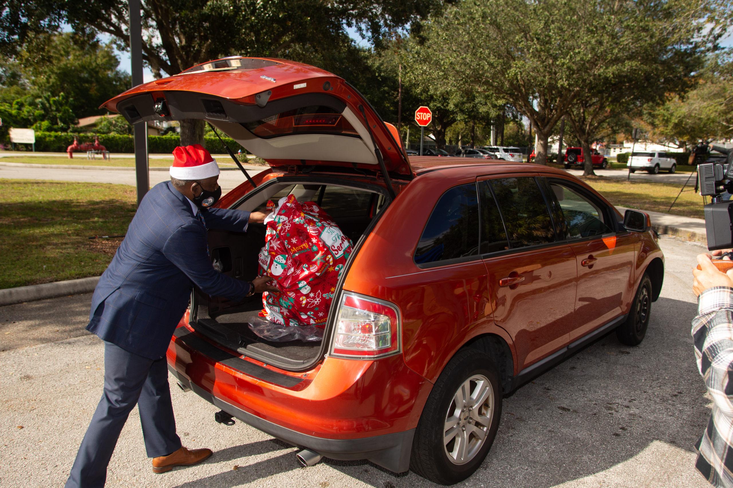 El Alcalde Demings carga juguetes dentro de un auto para la colecta de juguetes.
