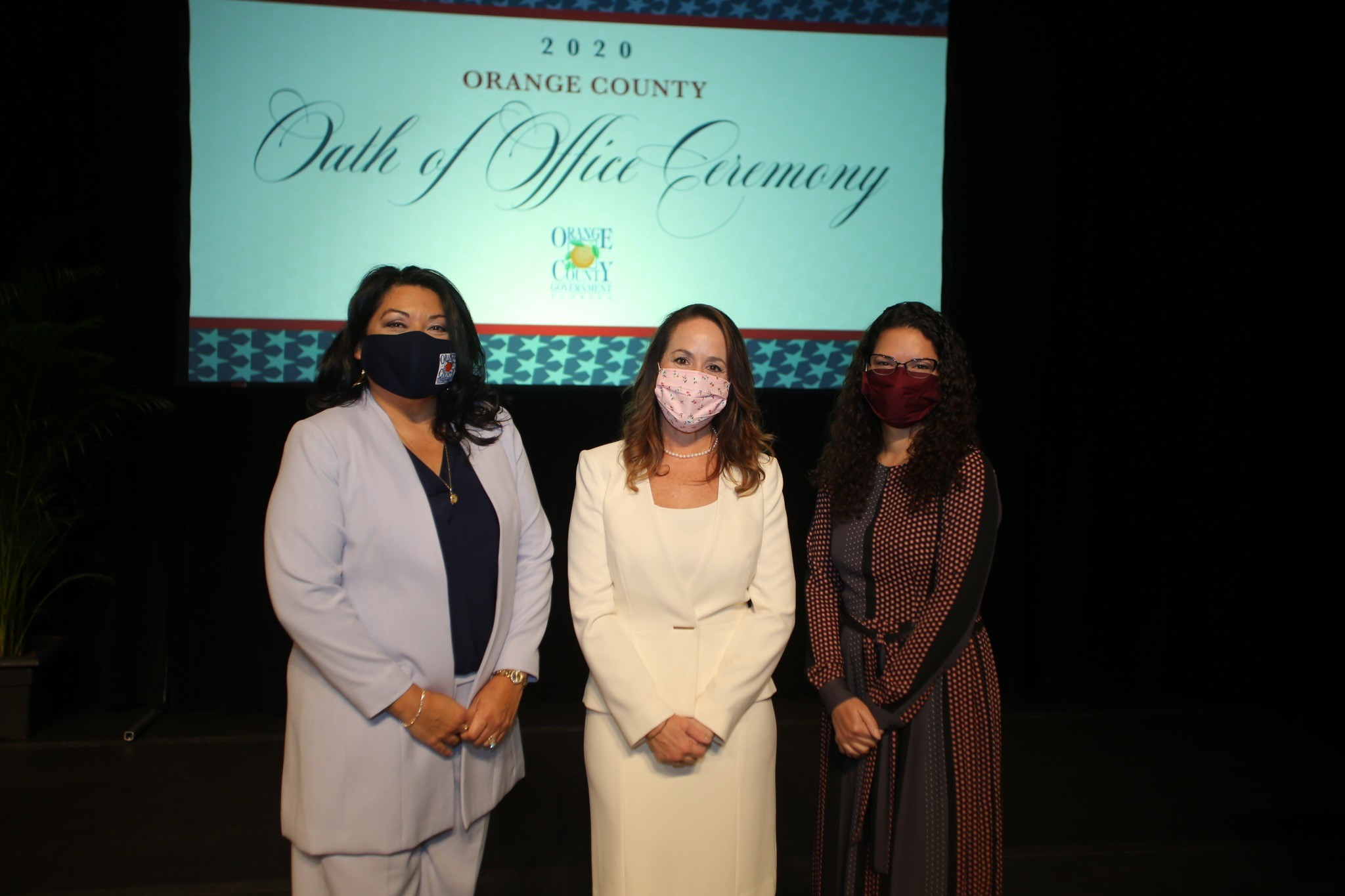 """Three orange county commissioners posing for a photo in front of a screen that reads """"2020 Oath of office Ceremony"""""""