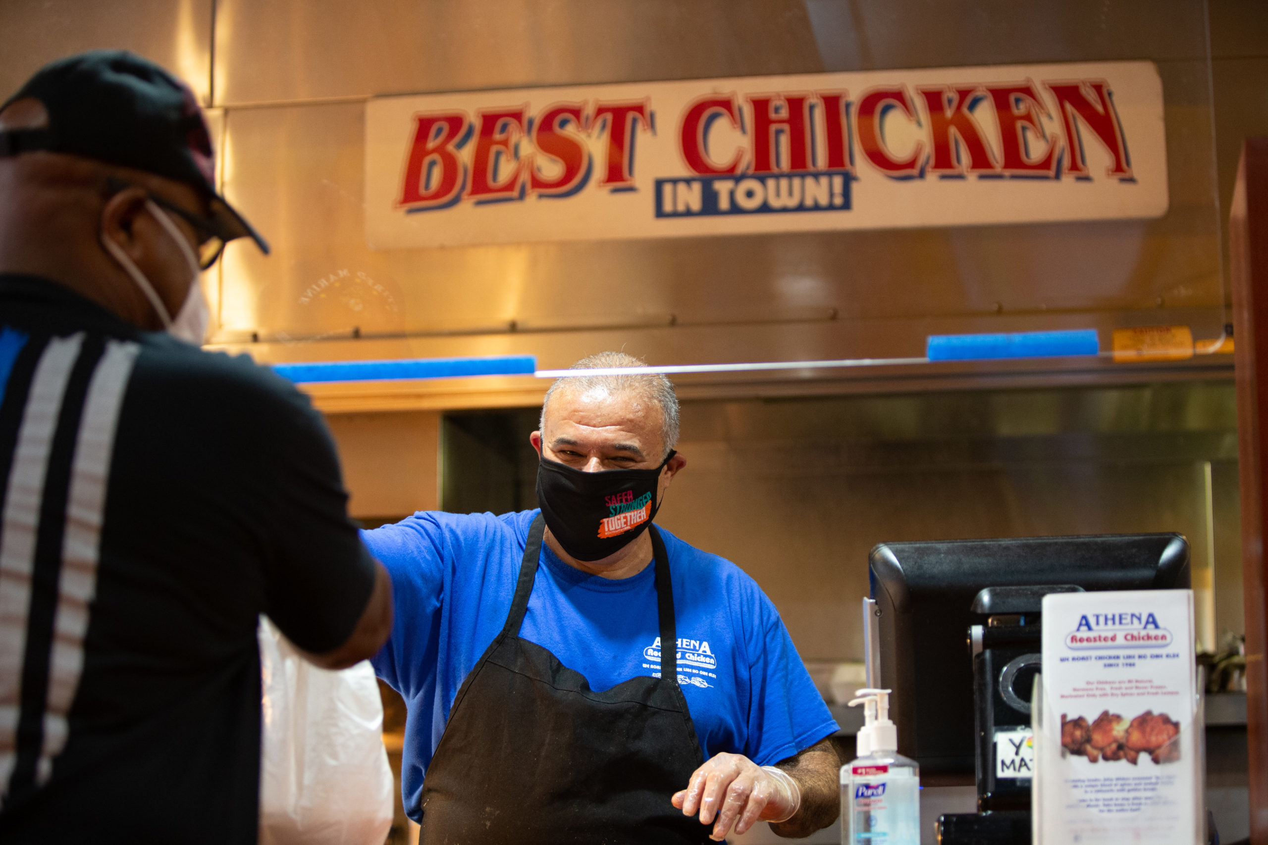 Man in mask and gloves smiling and serving food