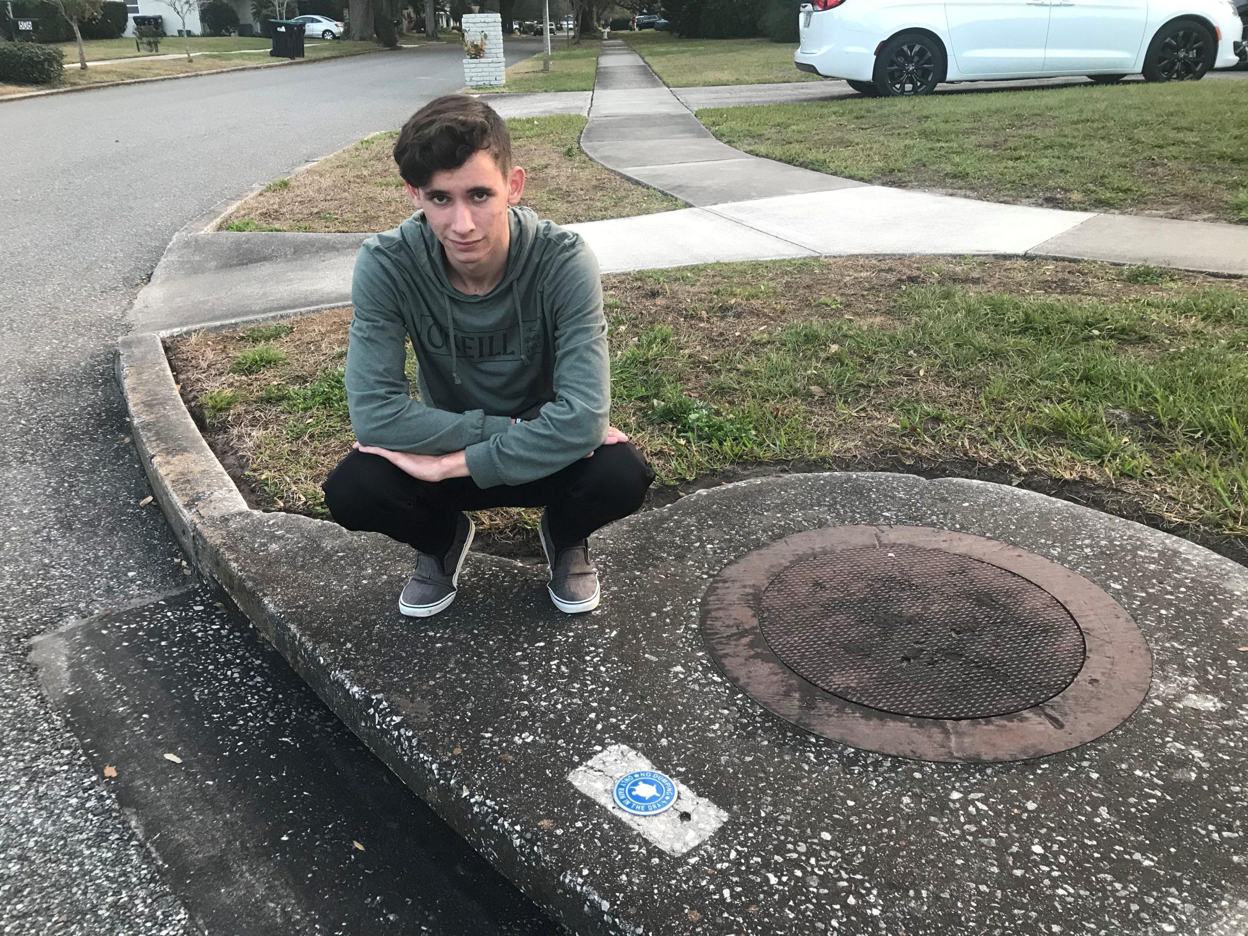 High school student installing a drain label.