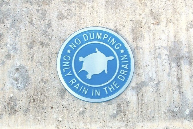 """Blue metal medallions bearing the phrase """"No Dumping—Only Rain in the Drain"""