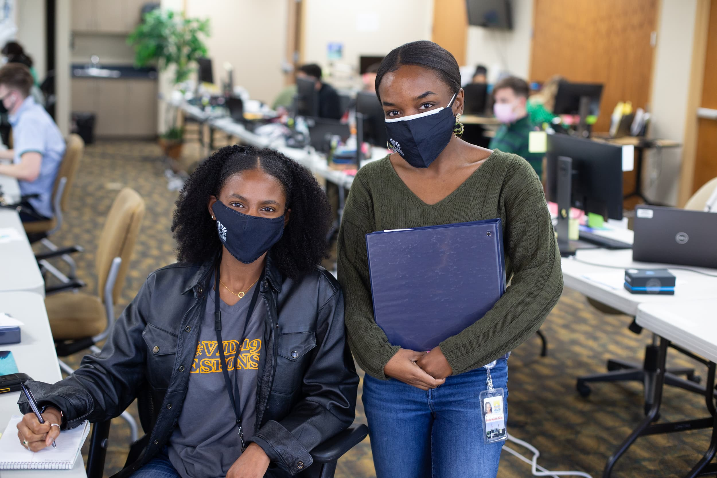 Two women wearing masks and holding a work binder