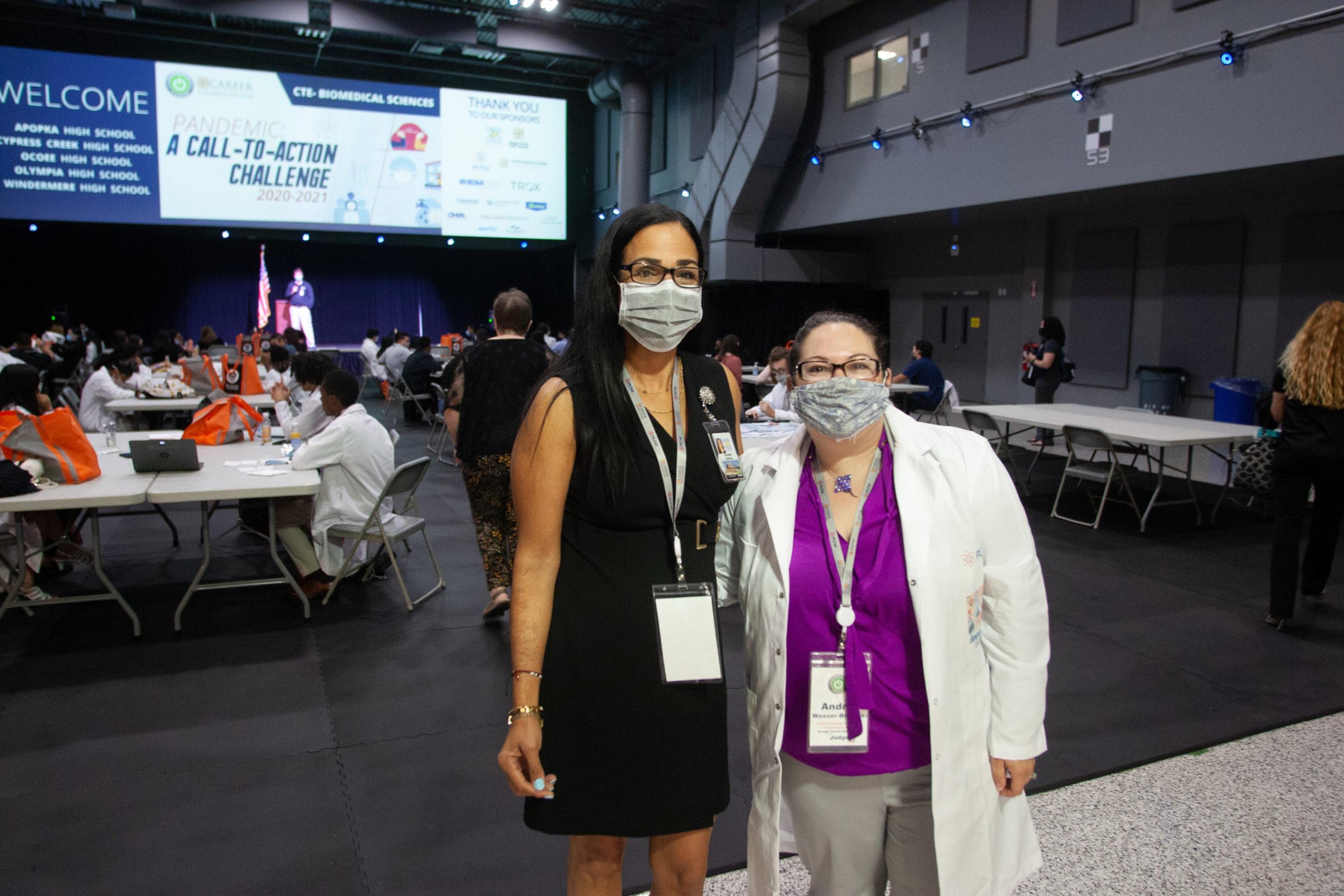 Dos mujeres posando para una foto dentro de una gran sala de conferencia
