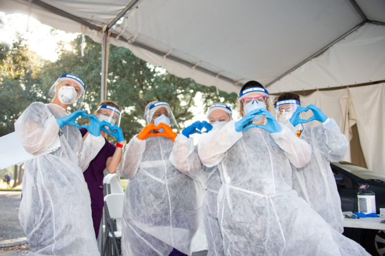Medical professionals in personal protective equipment making heart shapes with their hands,