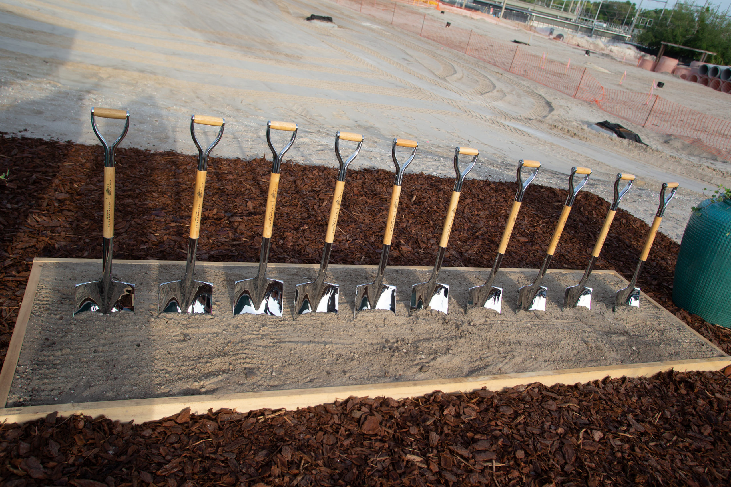 A row of partially dug-in shovels marking the groundbreaking of a project
