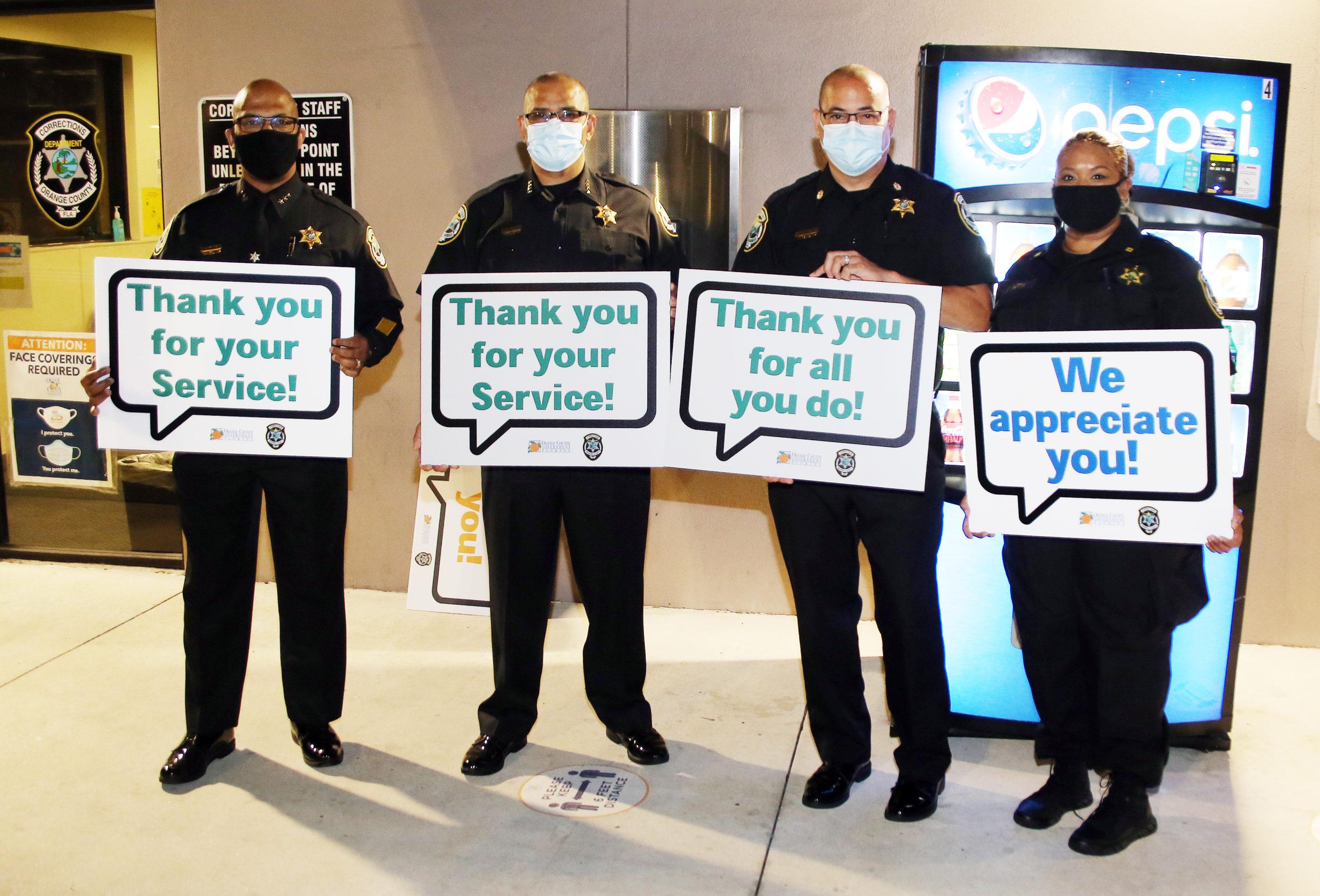 Los encargados de darles la bienvenida sostienen carteles de agradecimiento por la Semana Nacional de los Oficiales y Empleados de Correccionales