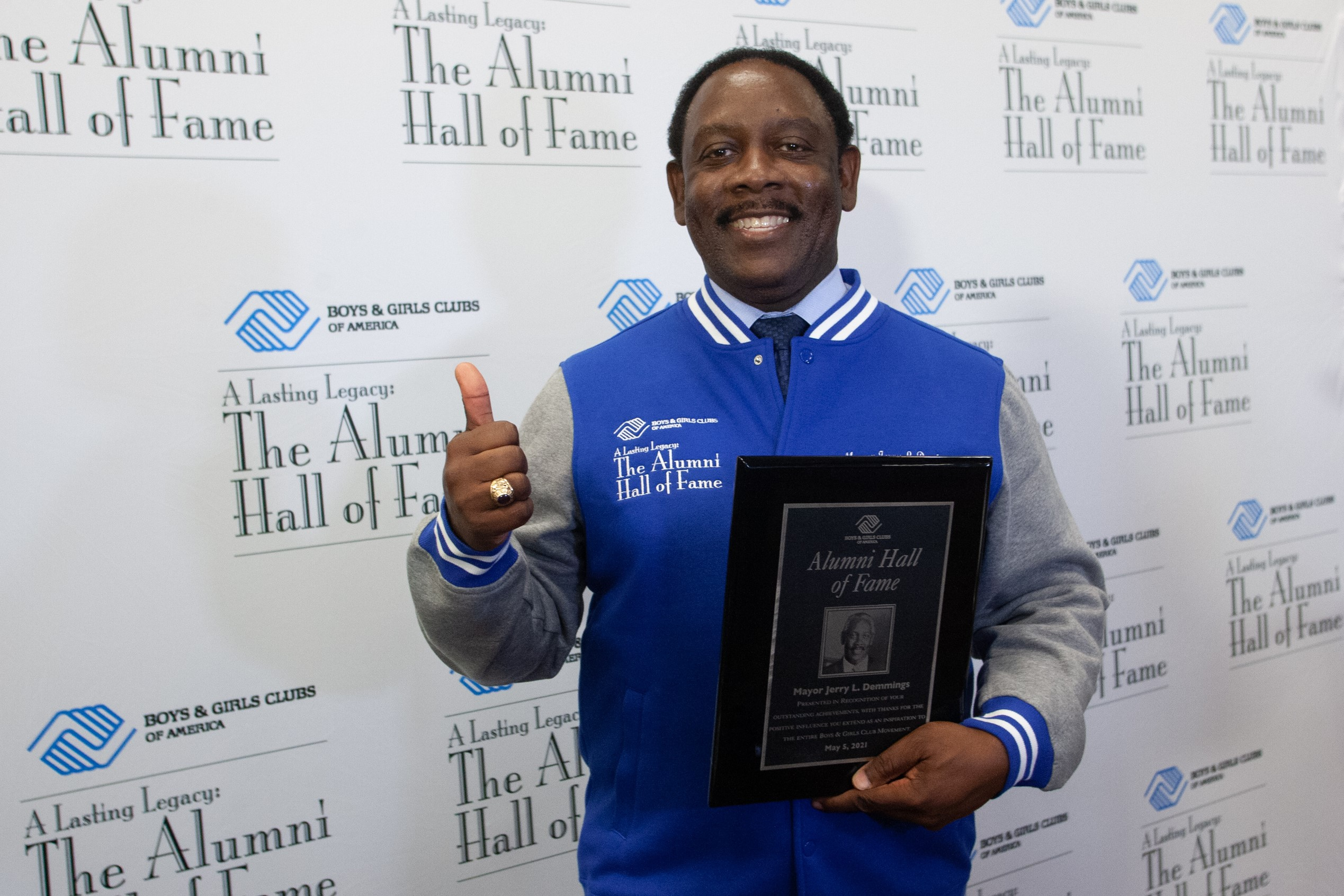 Mayor Demings in a blue jacket holding Alumni Hall of Fame Award giving a thumbs up