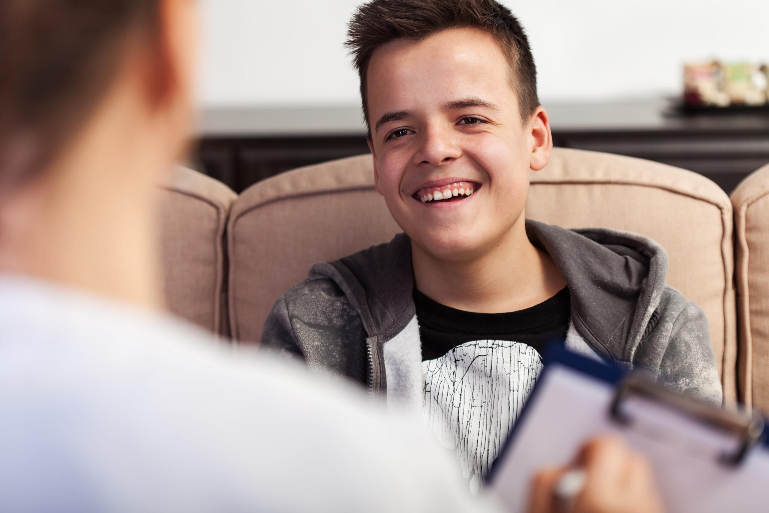 Un joven adolescente sonriendo con su consejero profesional en primer plano,