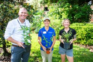 Voluntarios sosteniendo plantas aptas para Florida.