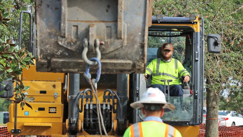 Construction workers operating machinery