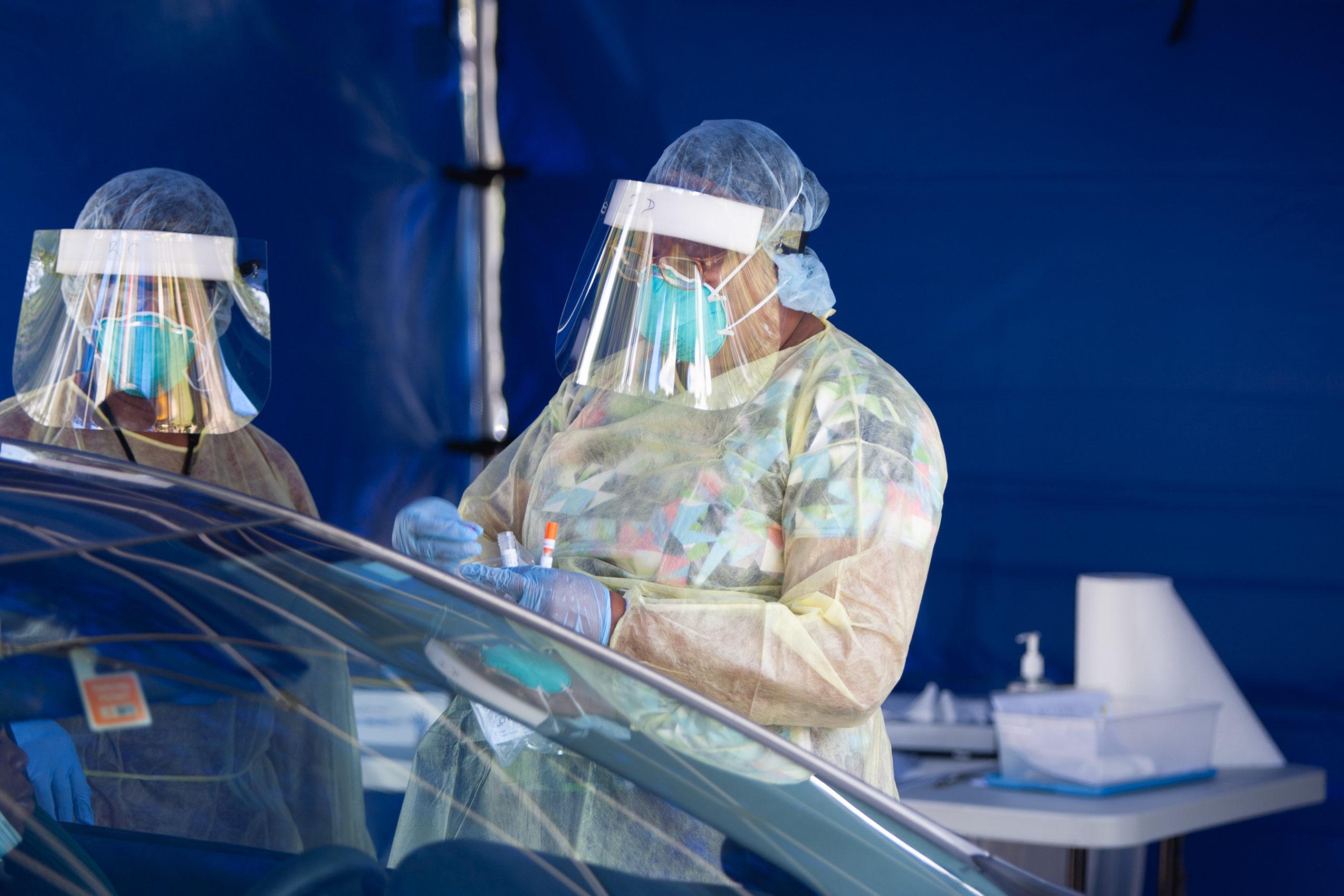 Enfermera con EPP sosteniendo una prueba de detección de COVID-19