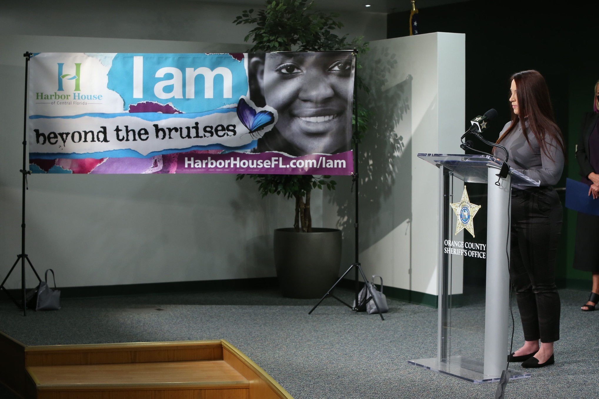 Woman speaks at podium in from of Domestic Violence Awareness Poster